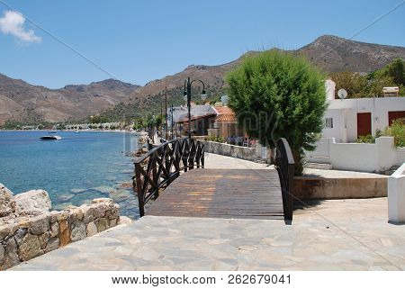 TILOS, GREECE - JUNE 17, 2018: A wooden footbridge on the seafront path at Livadia on the Greek island of Tilos. The Dodecanese island has a population of around 780 people.