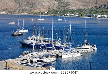 TILOS, GREECE - JUNE 12, 2018: Ferry boat Panagia Spiliani and other boats moored at Livadia harbour on the Greek island of Tilos. The Dodecanese island has a population of around 780 people.