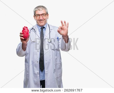 Handsome senior cardiologist doctor man holding heart over isolated background doing ok sign with fingers, excellent symbol