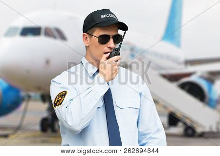 Portrait Of A Male Security Guard Talking On Walkie Talkie At An Airport poster
