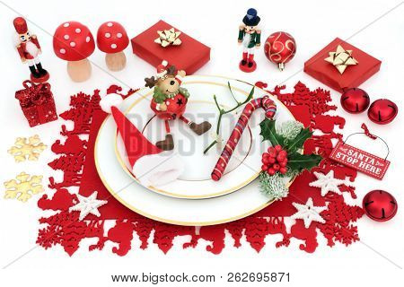 Christmas dinner fun place setting with porcelain plates, bauble decorations and winter flora on red place mat on white background. Festive themed concept.