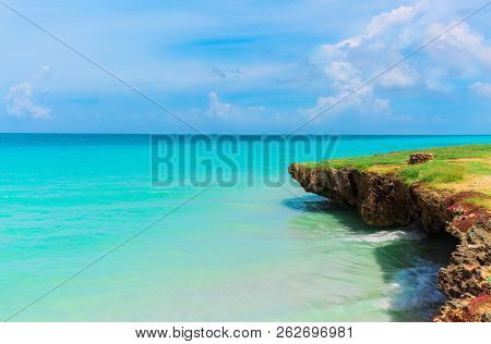 Natural Amazing Beautiful Landscape View On Tranquil Turquoise Ocean And Cliff With Blue Cloudy Sky