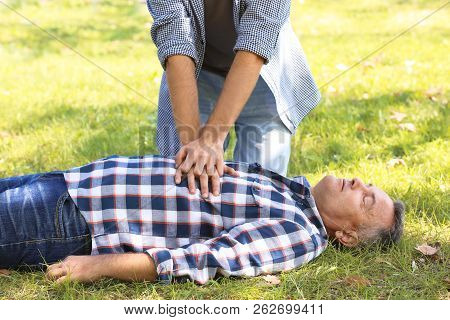 Passerby Performing Cpr On Unconscious Man Outdoors. First Aid