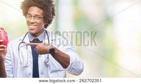 Afro american cardiologist doctor man over isolated background very happy pointing with hand and finger