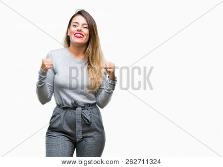 Young beautiful worker business woman over isolated background excited for success with arms raised celebrating victory smiling. Winner concept.