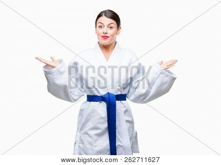 Young beautiful woman wearing karate kimono uniform over isolated background clueless and confused expression with arms and hands raised. Doubt concept.