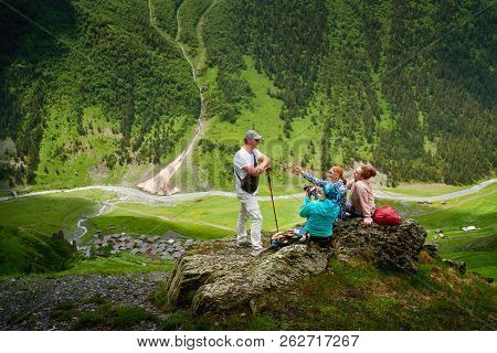 Group Of Tourists Enjoying During Summer Vacation In Mountains Near Old Ancient Village Dartlo. Tush