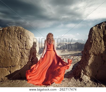 Woman In Long Red Dress On The Edge Of A Cliff In The Mountains  Looking To Sunny Valley.  Girl On T