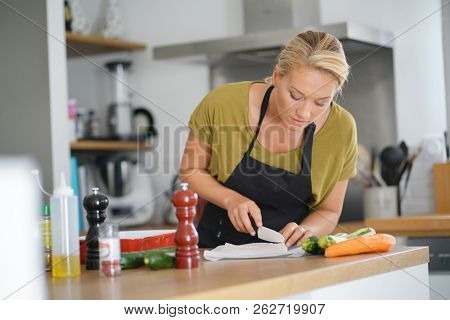 40-year-old woman cooking in home kitchen