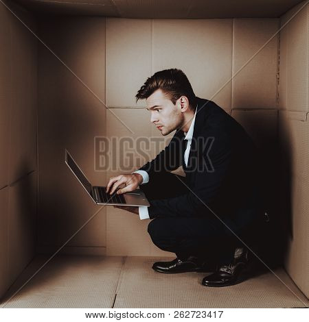 Young Businessman with Laptop in Cardboard Box. Young Man in Suit. Life in Little Cardboard Box. Uncomfortable Life. Personal Spase Concepts. Using Digital Device. Young Introvert. poster