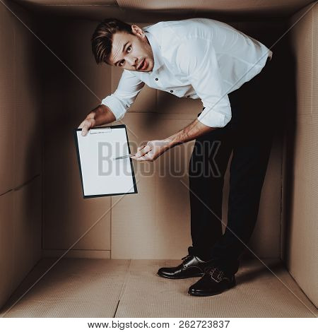 Young Businessman with Notebook in Cardboard Box. Young Man in White Shirt. Life in Little Cardboard Box. Uncomfortable Life. Personal Spase Concept. Uncomfortable House Concept. Young Introvert. poster
