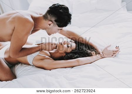 Young Beautiful Couple In Underwear Lying On Bed. Handsome Man Touching Chin Of Attractive Woman. Pa