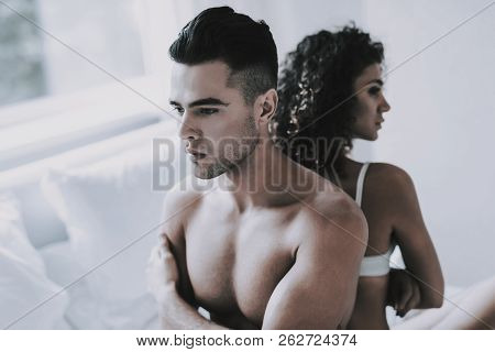 Young Unhappy Couple Arguing In Bed At Home. Handsome Man And Beautiful Woman Having Conflict In Bed