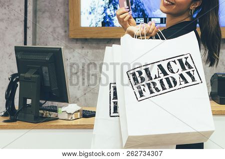 Black Friday. Cropped View Of A Female Shopper Using Credit Card To Pay The Purchase While Is Holdin