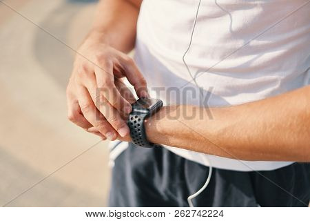 Person Using Smart Watch. Young Runner Man Making Gestures On A Wearable Smart Watch Computer Device