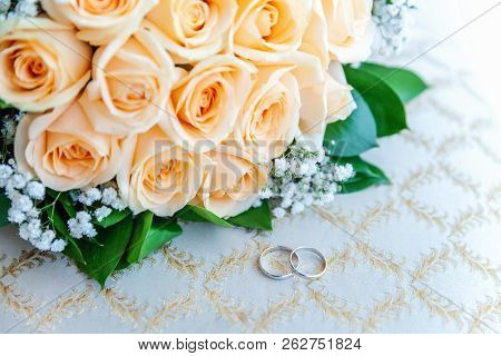 Beautiful Wedding Rings Lie On Light Surface Against Background Of Bouquet Of Flowers. Declaration O