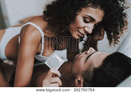 Young Beautiful Couple In Underwear Lying On Bed. Attractive Woman Sitting On Handsome Man And Holdi