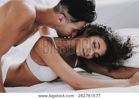 Young Beautiful Couple In Underwear Lying On Bed. Handsome Man Kissing Attractive Woman. Passionate