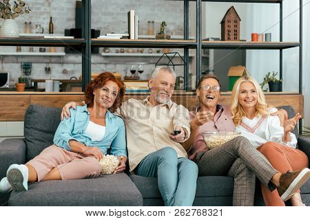 Happy Mature Friends Laughing And Eating Popcorn And Watching Tv Together