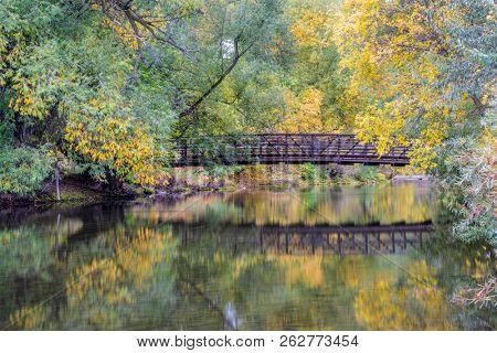 footbridge over a river in fall scenery  - Cache la Poudre River in Fort Collins, Colorado