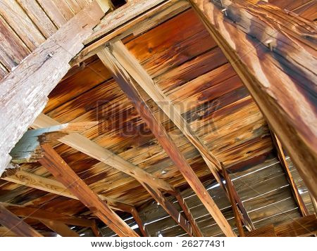 Abandoned old house surrounded by beautiful blue sky and desert sands. Decaying wooden structures show weathering from desertion.