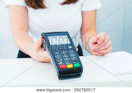 Seller Holds Payment Terminal In Hands. Contactless Payment With Nfc Technology At Shop, Clinic, Hot