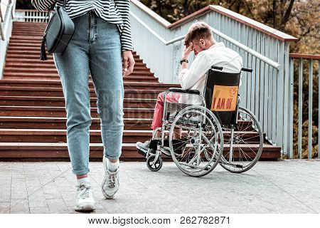 Young Woman Passing Disabled Man And Not Helping Him