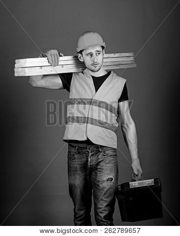 Construction And Woodworking Concept. Man In Helmet, Hard Hat Holds Toolbox And Wooden Beams, Grey B