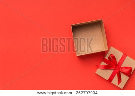 Open Gift Box With Ribbon Bow On Red Background Top View