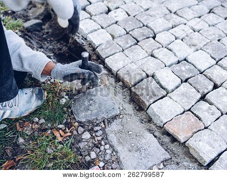 Construction Worker Placing Stone Tiles For Pavement, Terrace. Worker Placing Granite Cobblestone Pa