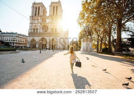 Morning View On The Famous Notre-dame Cathedral With Woman Running On The Square Dispersing Pigeons