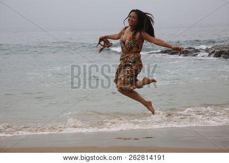 Vietnamese woman enjoys the beach. A young Vietnamese woman enjoys a day at the beach. Laguna Beach California