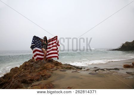 Woman with American Flag. A beautiful woman with an American flag at the beach. red white and blue stars and stripes flag. Vietnamese American Woman with American Flag.