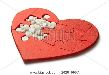 Heart Puzzle Red And White Pills Isolated On White Background. Concept Treatment Of Heart Disease Pi