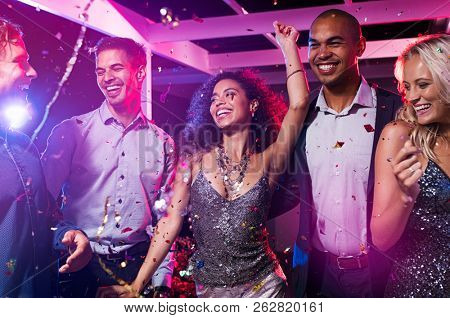 Group of multiethnic happy friends dancing at disco club. Group of young men and beautiful women having fun at celebration with confetti. Smiling guys and elegant girls enjoying night life.