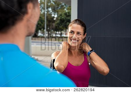 Happy mature fitness couple outdoors on cirty street. Smiling woman jogging and adjusting earphones while looking at man. Portrait of middle aged sports woman resting after run.