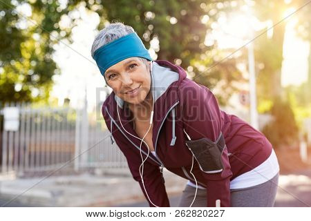 Senior active woman completing her daily routine workout. Portrait of athletic mature woman resting after jogging at park during sunset. Elderly runner listening to music while resting after running.