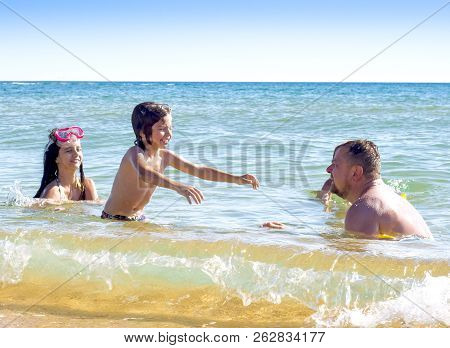 Family On Summer Beach Vacation Lying In The Water And Enjoying Each Others Company.happy Family Vac