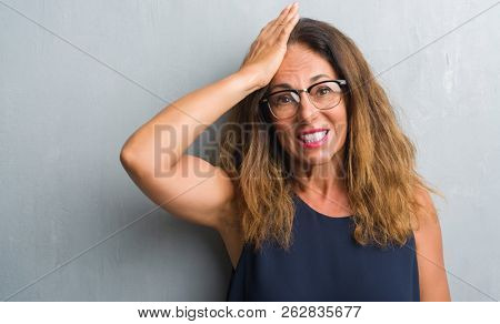 Middle age hispanic woman over grey wall wearing glasses stressed with hand on head, shocked with shame and surprise face, angry and frustrated. Fear and upset for mistake.