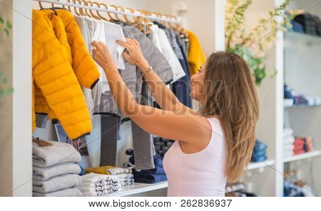 Beautiful middle age hispanic woman standing with smile on face at clothes store. Shop owner and shop assistant smiling confident and cheerful. Client buying.