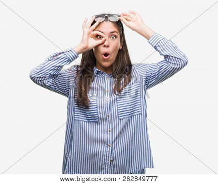 Young beautiful hispanic business woman doing ok gesture shocked with surprised face, eye looking through fingers. Unbelieving expression.