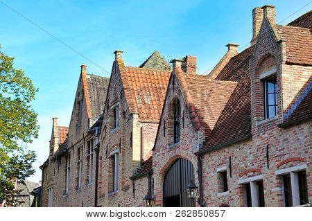 Attractive Traditional Warm Brick House Frontages And Roofs In The Center Of Bruges In October