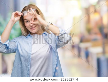Young caucasian business woman wearing glasses over isolated background doing ok gesture with hand smiling, eye looking through fingers with happy face.