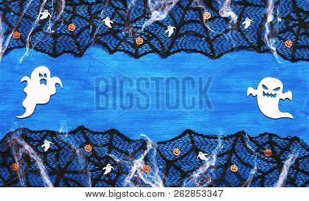 Halloween background - spider web lace, ghosts, ghosts and smiling jack decorations as symbols of Halloween on the dark blue wooden background. Halloween festive concept, Halloween design