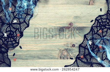 Halloween festive border background. Spider web, black cobweb lace and decorations as the symbols of Halloween holiday on the wooden background, Halloween design