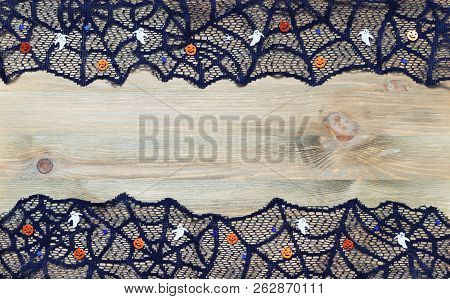 Halloween border background. Halloween decorations aand black lace cobweb on the dark wooden background with free space for Halloween text