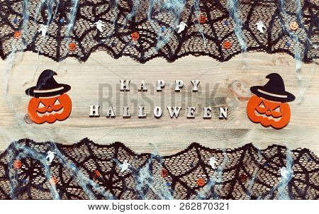 Halloween festive background in retro tones. Happy Halloween letters and Halloween decorations on the dark wooden background, Halloween design