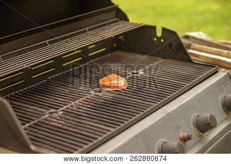 Seasoned Steak On Gas Grill With Cooking Tools