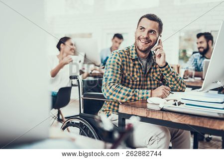 Man On Wheelchair Write Notes And Talking On Phone. Disabled Young Man. Man On Wheelchair. Recovery