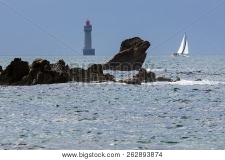 The Jument lighthouse and a sailboat, Ushant island, Brittany, France